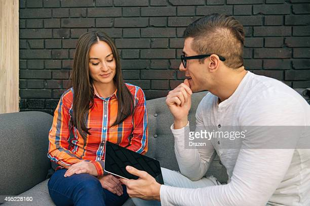 young couple sitting on sofa and looking at digital tablet - drazen stock pictures, royalty-free photos & images