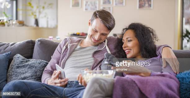 young couple sitting on sofa and using mobile phone - changing channels stock photos and pictures