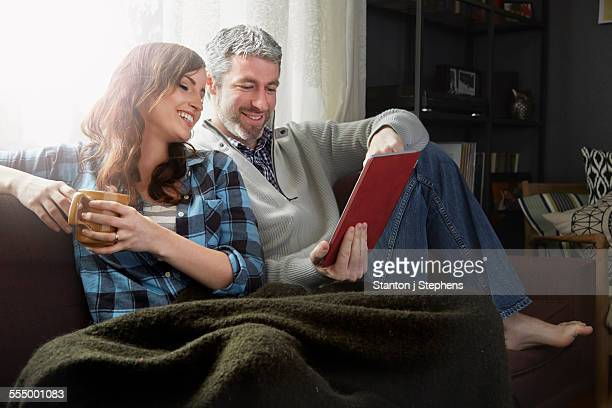 young couple sitting on sofa drinking coffee and looking at digital tablet - hot couple photos et images de collection