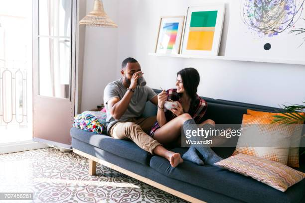 young couple sitting on sofa, eating breakfast - young couples stock pictures, royalty-free photos & images