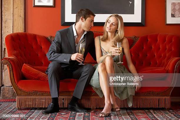 young couple sitting on sofa holding champagne flutes - côte à côte photos et images de collection