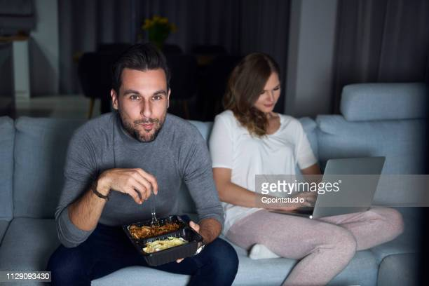 Young couple sitting on sofa in evening eating takeaway and using laptop