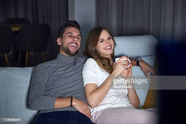 Young couple sitting on sofa in evening, laughing while watching TV