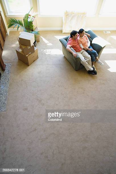 Young couple sitting on sofa in new home, elevated view