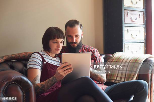 young couple sitting on sofa using digital tablet - heterosexual couple photos stock photos and pictures