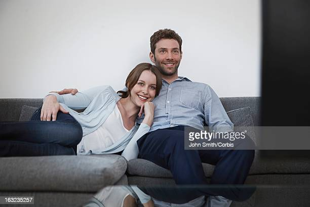 Young couple sitting on sofa, watching television