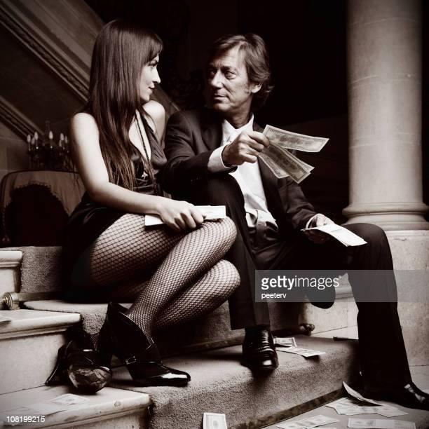 pareja joven sentado en escalera de retención de fondos - pareja hombre mayor y mujer joven fotografías e imágenes de stock