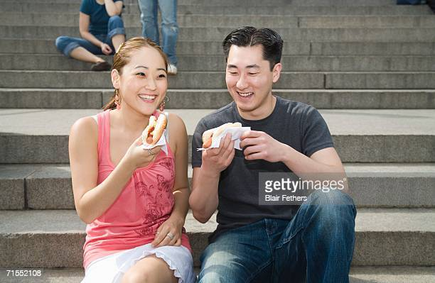 Young couple sitting on steps eating hot dogs, New York City