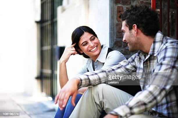 Junges Paar sitzt auf der Straße