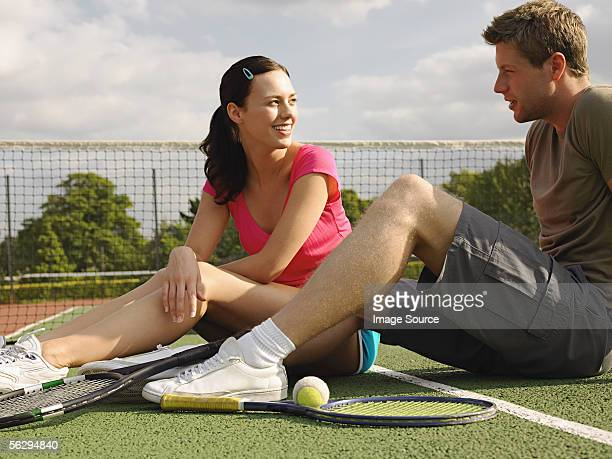 Young couple sitting on tennis court