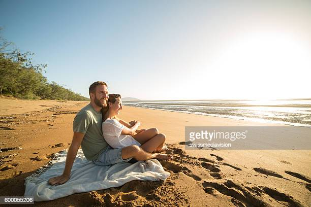 Young couple sitting on the beach watching sunset