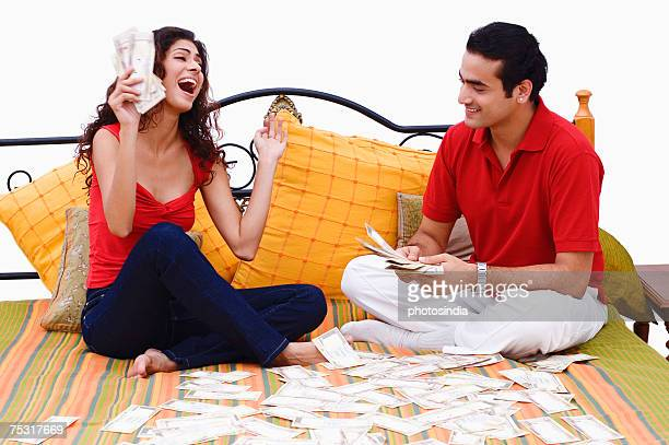 Young couple sitting on the bed and sharing paper currency