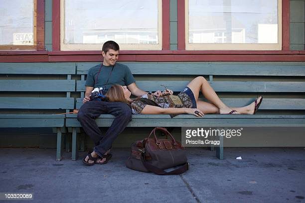 Young couple sitting on the bench waiting for the bus.
