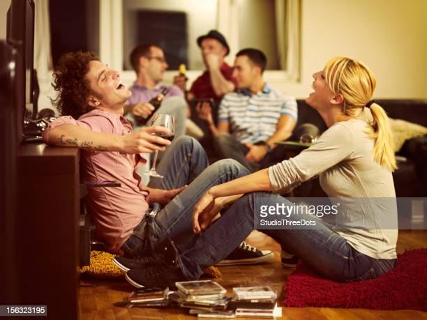 Pareja joven sentada en el piso mirando televisión