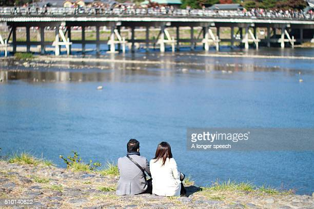 A young couple sitting on the river bank in Kyoto