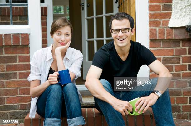 A young couple sitting on their doorstep
