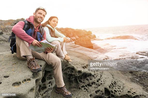 Young couple sitting on top of rocks
