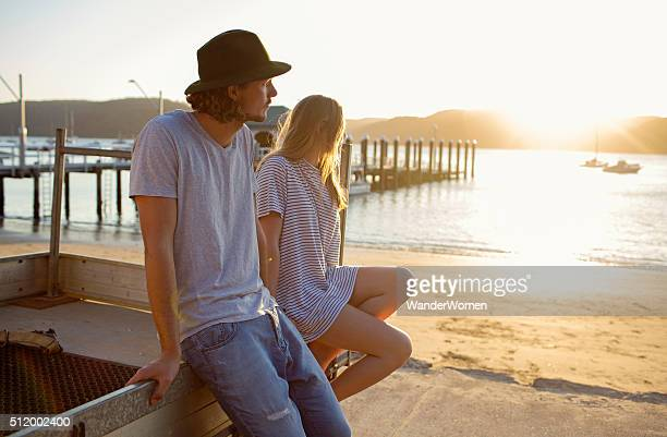 young couple sitting on tray back of ute at sunset - pier stock pictures, royalty-free photos & images