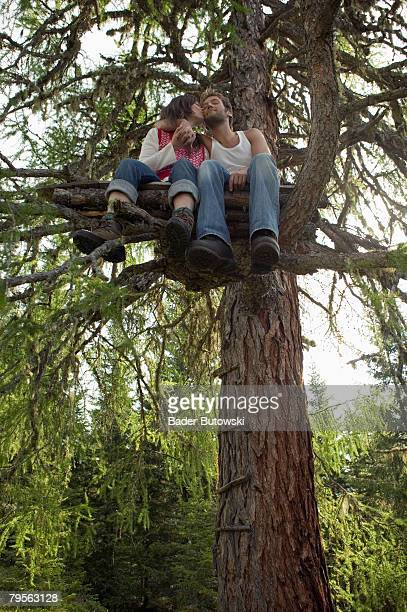 'Young couple sitting on tree house, kissing, low angle view'