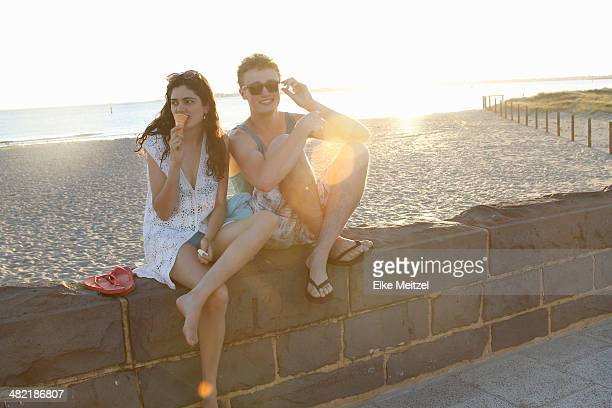 Young couple sitting on wall, Port Melbourne, Melbourne, Australia