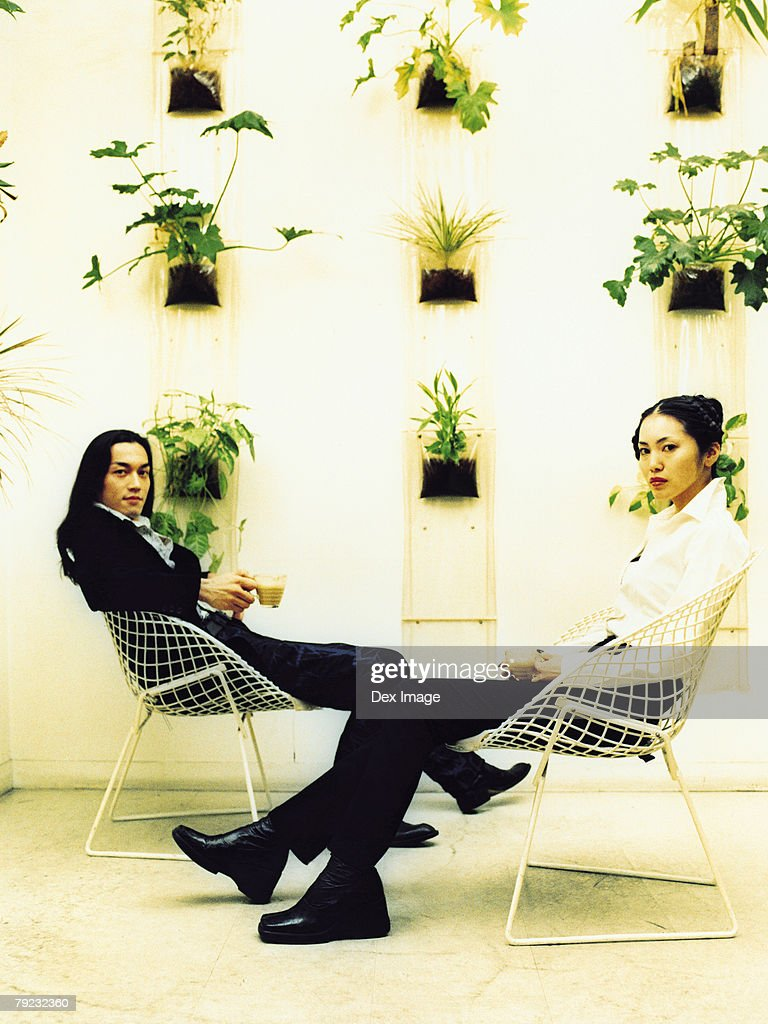 Young couple sitting on wire-framed chairs, potted plants decorated wall background : Stock Photo