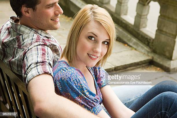 """a young couple sitting outdoors together - """"compassionate eye"""" stock pictures, royalty-free photos & images"""