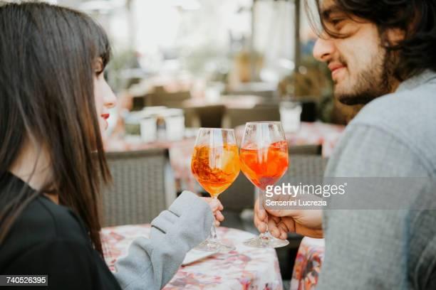 young couple sitting outside cafe, holding drinks, making a toast - muro stock photos and pictures