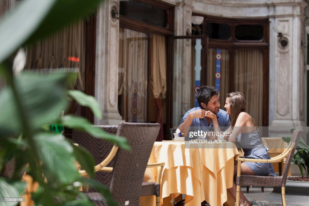 Young couple sitting outside cafe, Turin, Piedmont, Italy : Stock Photo