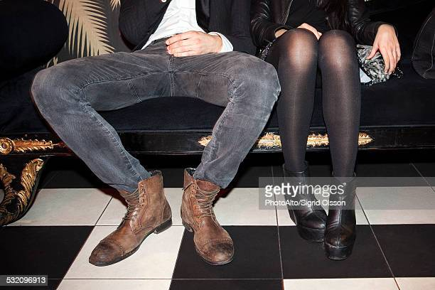 young couple sitting side by side at night club - benen gespreid stockfoto's en -beelden