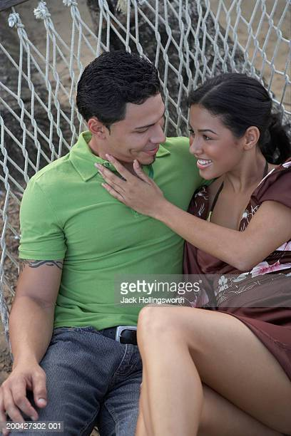 Young couple sitting together in a hammock
