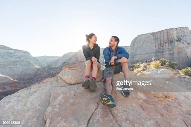 pareja de jóvenes sentados juntos en un acantilado - flanco de valle fotografías e imágenes de stock
