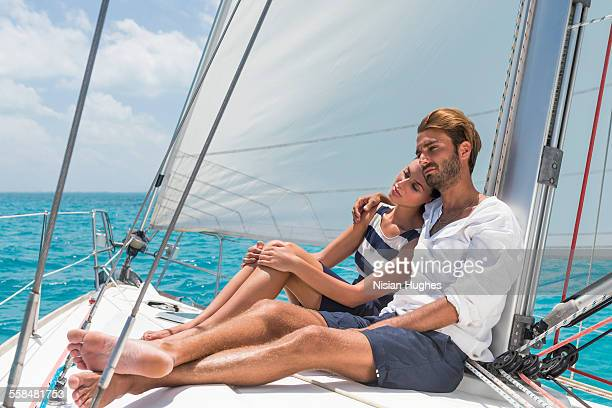 young couple sitting together on sailboat - hot women on boats stock pictures, royalty-free photos & images
