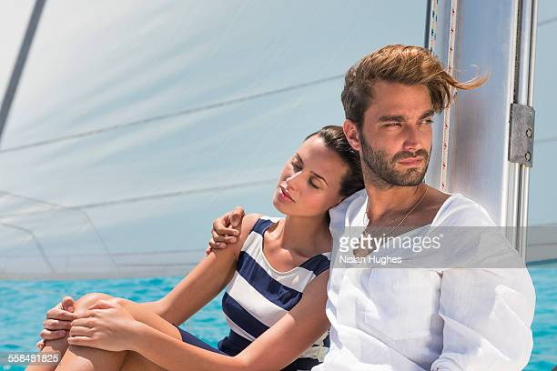 Young couple sitting together on sailboat