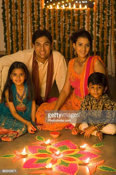 Young couple sitting with their children in front of rangoli