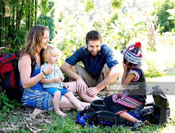 Young couple sitting with their son (12-23 months) and local child (4-5), Chiang Mai, Thailand