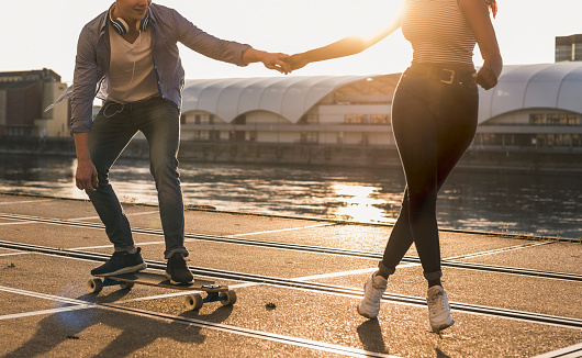 Young couple skateboarding at the riverside - gettyimageskorea