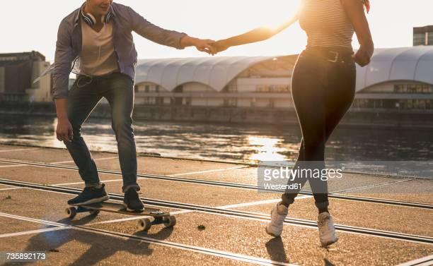 young couple skateboarding at the riverside - mannheim stock-fotos und bilder