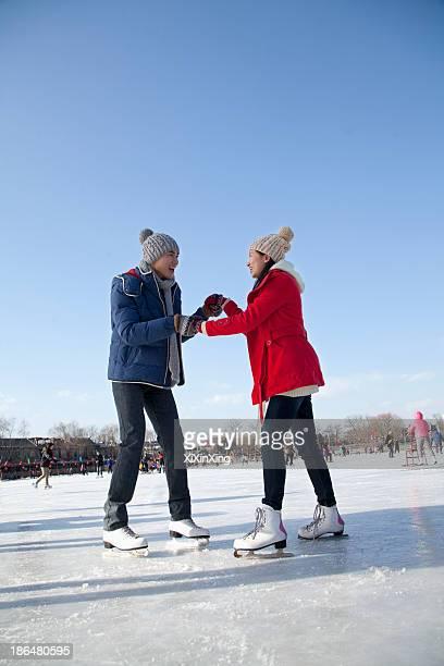 Young couple skating at ice rink
