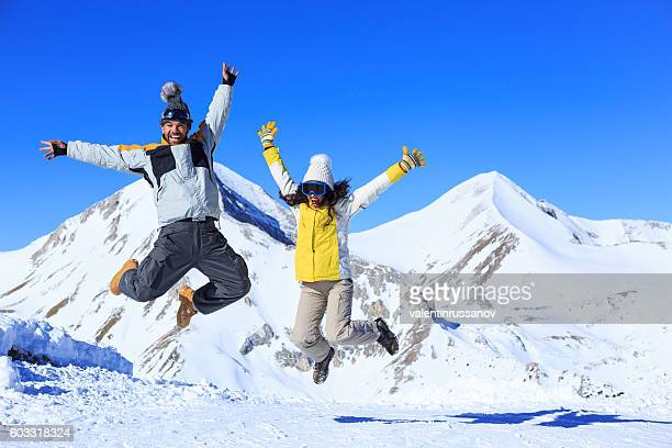 Young couple skiers having fun and jumping on snow mountain