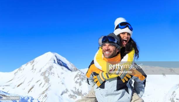 jong (echt) paar skiërs plezier op top sneeuw berg - wintersport stockfoto's en -beelden