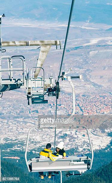 Young couple skiers sitting on chairlift in ski resort