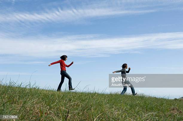Young couple skipping in field