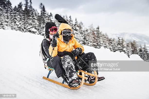 young couple sledging, bramberg am wildkogel, austria - schlitten stock-fotos und bilder