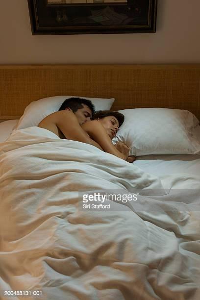 young couple sleeping in bed - abbracciarsi a letto foto e immagini stock