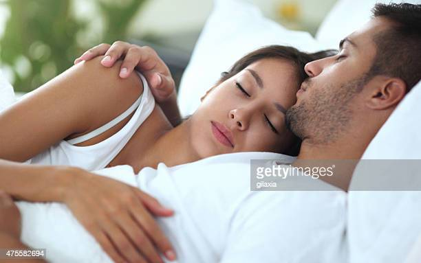 young couple sleeping in bed. - couple cuddling in bed stock photos and pictures