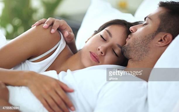 pareja joven durmiendo en la cama. - pareja abrazados cama fotografías e imágenes de stock