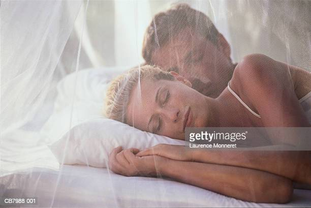 Young couple sleeping in bed, view through mosquito net