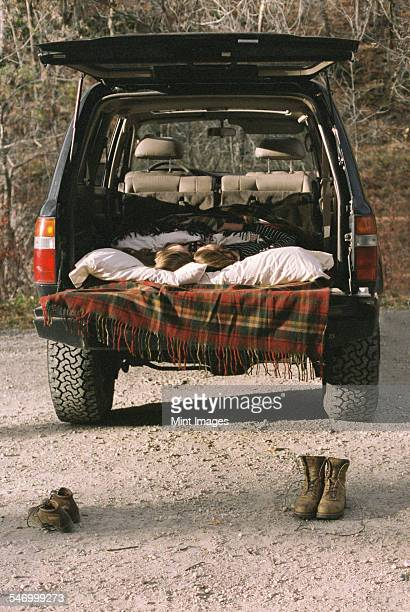 Young couple sleeping in the back of their car, boots standing on the ground in foreground.