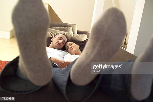 Young couple sleeping on sofa with their feet up
