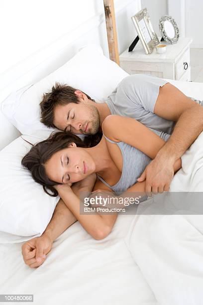 young couple sleeping - abbracciarsi a letto foto e immagini stock